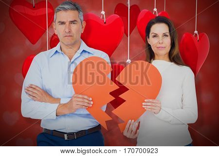 Portrait of couple holding broken heart shape paper against valentines heart design 3d