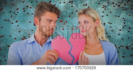 Couple holding two halves of broken heart against blue paint splashed surface