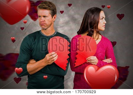 Serious couple holding cracked heart shape against love heart pattern 3d