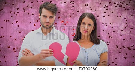 Upset couple holding two halves of broken heart against pink paint splashed surface
