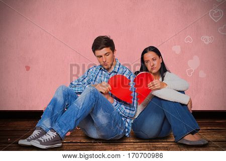 Young couple sitting on floor with broken heart against white background