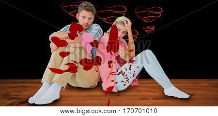 Attractive young couple sitting holding two halves of broken heart against red hearts floating