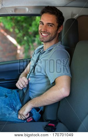 Portrait of handsome driver fastening car seat belt