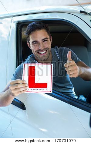 Portrait of handsome man showing thumbs up while holding L plate in car
