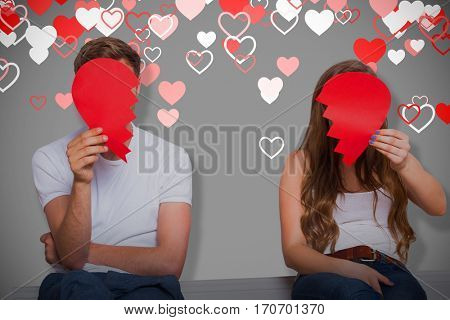 Couple holding broken heart against grey background