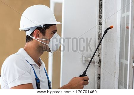 Side view of manual worker spraying pesticide on window
