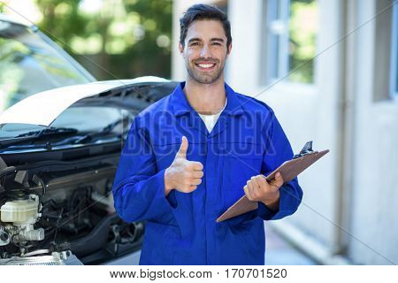 Portrait of confident engineer showing thumbs up sign while standing by van