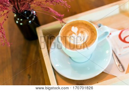 A cup of coffee latte art in Rosetta pattern with tree or flower in glass bottles on wooden background.