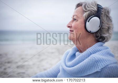 Senior woman listening to music on headphone at beach