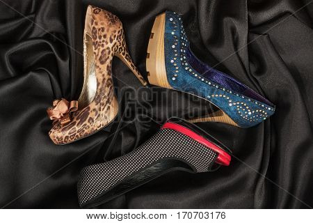 Three luxurious women's shoes with high heels lying on a black silk. View from above