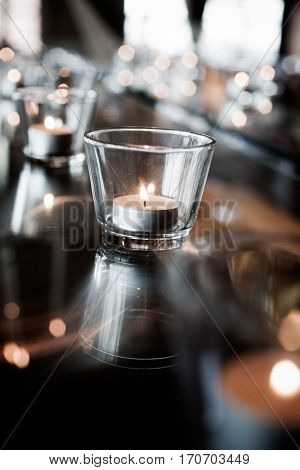 Tealights reflecting from glass table