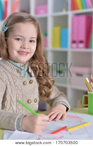 Portrait of a little girl drawing at her room