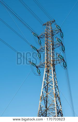 High voltage electrical power line pylon with blue sky as background