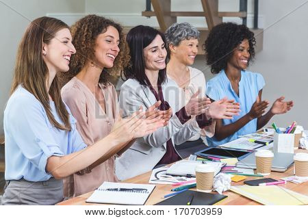 Group of interior designers applauding after listening to presentation in office