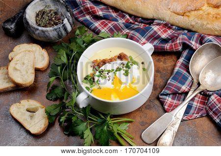 Garlic potato cream soup with bacon and poached eggs herbs spices
