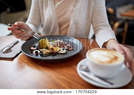 food, new nordic cuisine and people concept - woman eating chocolate ice cream dessert with blueberry kissel, honey baked fig and greek yoghurt with coffee at cafe