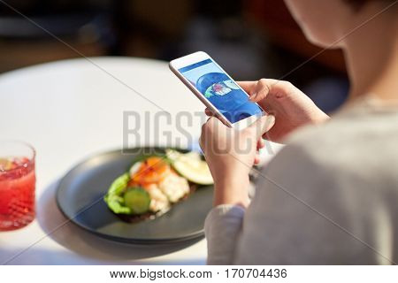 food, new nordic cuisine, technology and people concept - close up of woman with smartphone photographing toast skagen with shrimps, lemon mayonnaise, caviar and buttery bread at restaurant