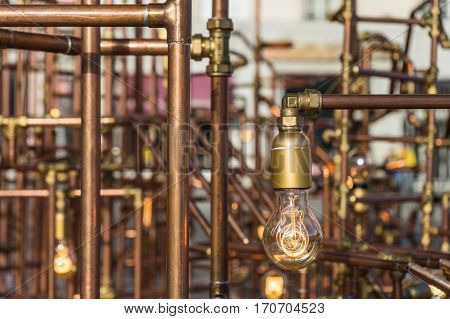 Vintage style light bulbs hang and decorated with alloy pipes in outdoor