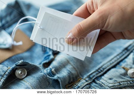 clothes, wear and fashion concept - close up of hand holding price tag of denim jacket