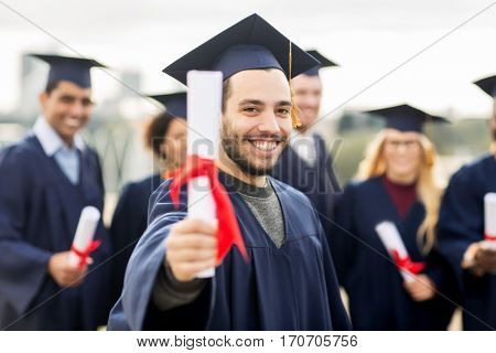 education, graduation and people concept - group of happy international students in mortar boards and bachelor gowns with diplomas poster