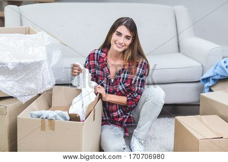 Portrait of beautiful woman unpacking carton boxes in his new house