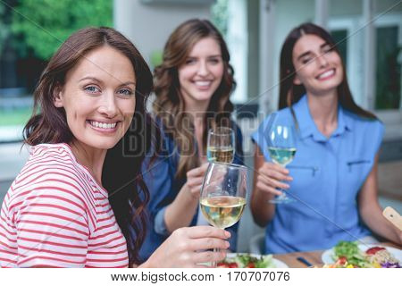 Portrait of friends holding glass of wine at home