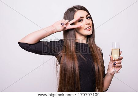 Young girl in black dress drink champagne on white background