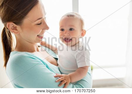 family, child and parenthood concept - happy smiling young mother with little baby at home