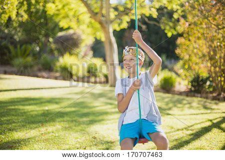 Happy boy swinging on swing in park