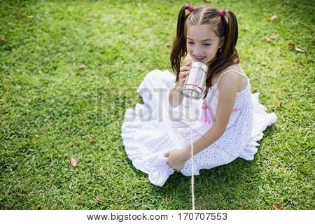 Cute young girl speaking through tin can phone in park