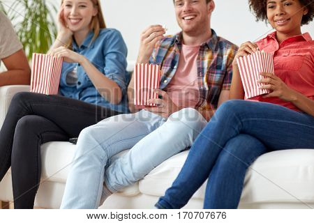 friendship, junk food and people concept - close up of happy smiling friends eating popcorn at home
