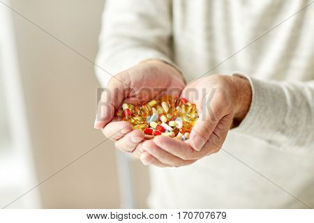 old age, medicine, drugs, healthcare and people concept - close up of senior man hands holding pills