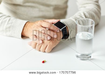 age, medicine, health care and people concept - close up of senior man with glass of water and pill looking at wristwatch