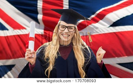 education, gesture and people concept - happy female student in mortar board and bachelor gown with diploma celebrating successful graduation over british flag background