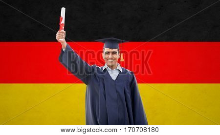 education, graduation and people concept - happy male student in mortarboard and bachelor gown with diploma over german flag background
