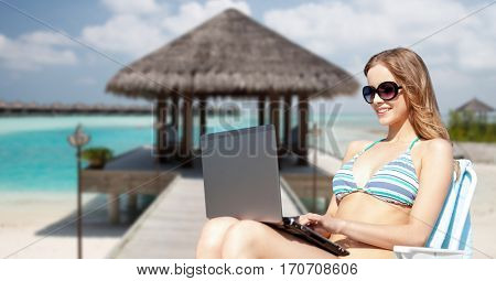 summer holidays, vacation, technology, people and internet - happy young woman in shades with laptop computer over exotic tropical beach and bungalow shed background