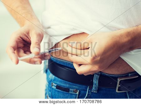 medicine, diabetes, glycemia, health care and people concept - close up of man with syringe making insulin injection to himself at home
