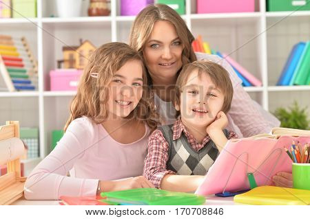 Mother helping her little son and teenage daughter with homework