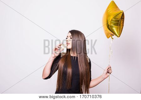 Woman In Black Dress With Star Shaped Balloon Drinking Champagne On White
