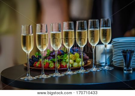 Dish with strawberries and champagne glasses on the table. Dinner, party, bachelorette party, summer party, celebration.