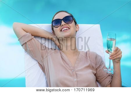 Business woman with a glass of champagne relaxing on sun lounger near pool