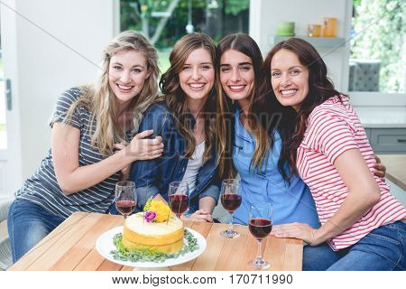 Portrait of beautiful women with birthday cake and glass of red wine at home