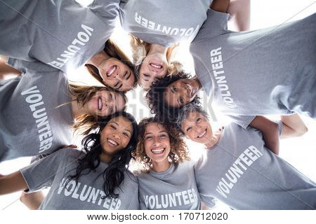 Happy volunteers forming a huddle against the sky