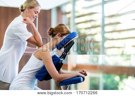 Woman receiving massage in massage chair at spa