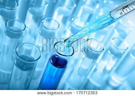 Closeup of a pipette dropping a sample into a test tube on blue background