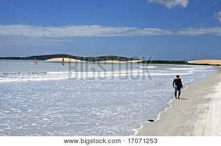 tourist walking on the beach of the beautiful fisherman village of Jericoacoara in ceara state brazil