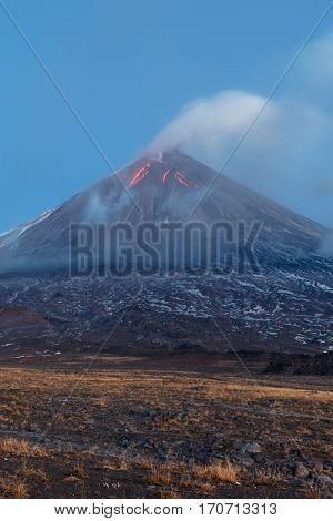 Volcanic landscape of Kamchatka: eruption Klyuchevskoy Volcano lava flows on of volcano; plume of gas steam ash from crater. Kamchatka Peninsula Russia Klyuchevskaya Group of Volcanoes.