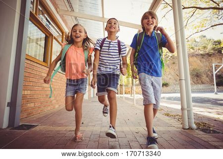 Happy school kids running in corridor at school