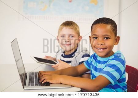 Portrait of smiling kids using a laptop and digital tablet in classroom at school