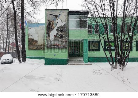 YELIZOVO CITY KAMCHATKA PENINSULA RUSSIA - JAN 5 2017: Aministration building of Kronotsky Nature Biosphere Reserve during snowfall and people coming out of building after visit to Museum of Nature